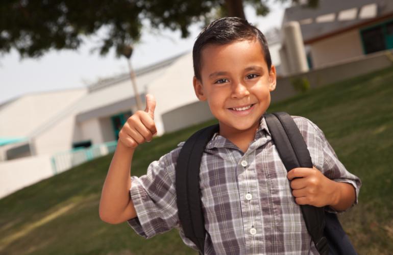 Kindergarten boy wearing a backpack giving a thumbs-up