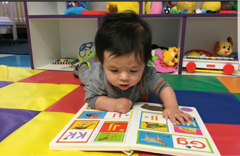 Baby looking at book on floor